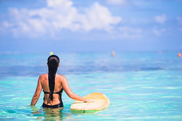 Hermosa mujer surfista surfeando durante las vacaciones de verano