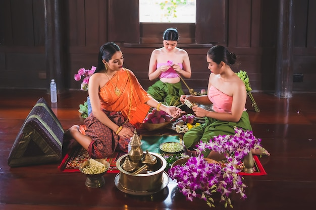 Una hermosa mujer tailandesa y ella viste trajes tradicionales tailandeses, tanto amos como sirvientes. están sentados preparando flores en una casa de madera para hacer méritos en el día del buda.
