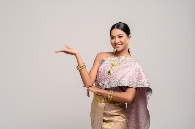 Hermosa mujer tailandesa usa ropa tailandesa y abre su mano a la derecha