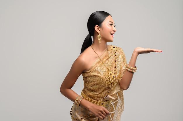 Hermosa mujer tailandesa usa ropa tailandesa y abre su mano a la izquierda