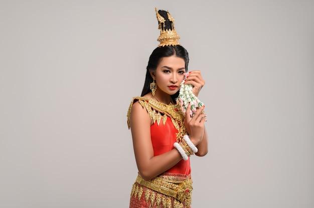 Hermosa mujer tailandesa con vestido tailandés y mirando hacia el lado