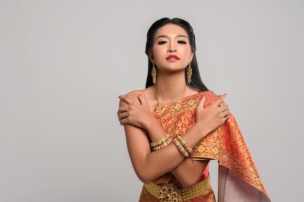 Hermosa mujer tailandesa con vestido tailandés y de pie abrazándose a sí misma