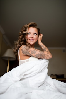 Hermosa mujer con tatuaje sonriendo en la cama.