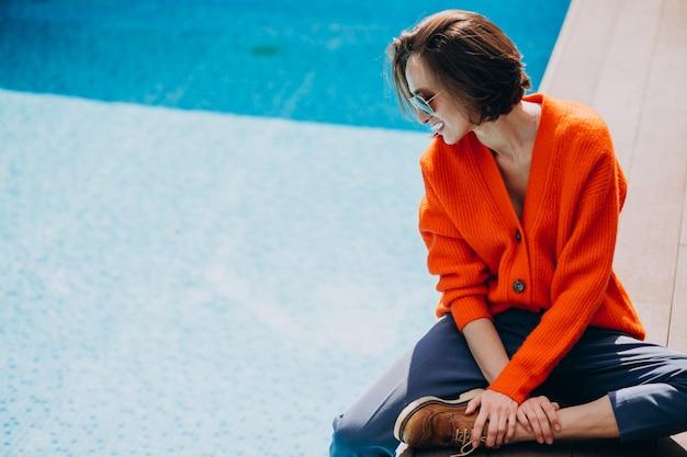 Hermosa mujer con teléfono sentado junto a la piscina