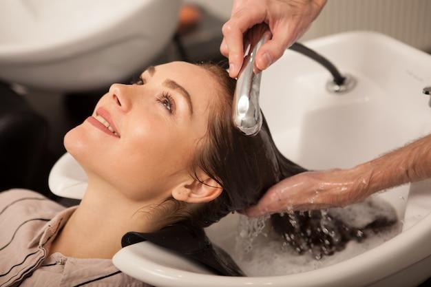 Hermosa mujer teniendo su cabello lavado por peluquero