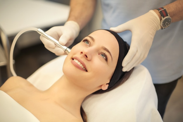 Hermosa mujer teniendo un tratamiento de la piel en una clínica