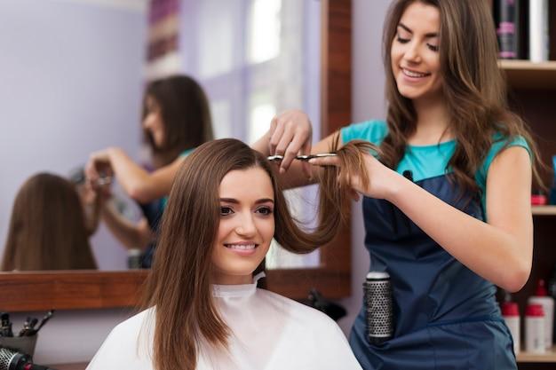 Hermosa mujer tiene corte de pelo en la peluquería