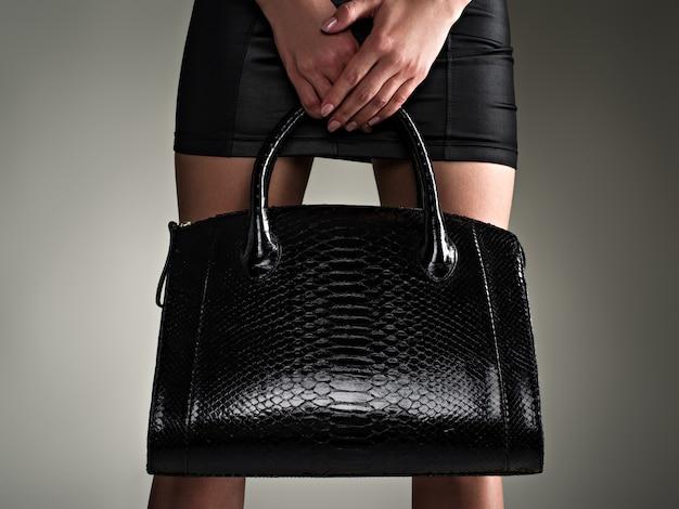 Hermosa mujer tiene elegante bolso negro. chica de moda. concepto de glamour elegante. arte. mujer después de ir de compras. mujer irreconocible.