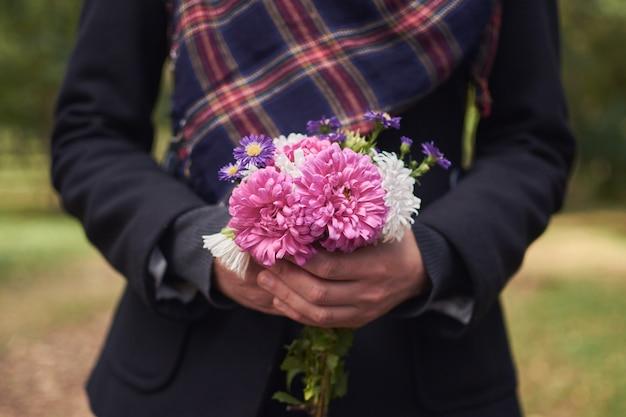 Hermosa mujer tiene flores silvestres en sus manos