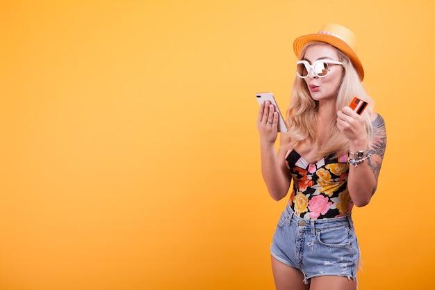 Hermosa mujer tiene teléfono inteligente y tarjeta de crédito en estudio sobre fondo amarillo