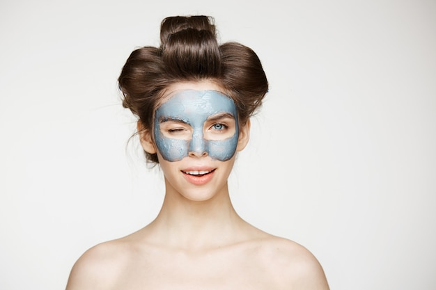 Hermosa mujer tierna desnuda en rizadores para el cabello y máscara facial guiño sonriente. tratamiento facial.