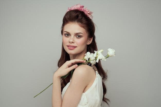 Hermosa mujer tierna primavera con flores en la mesa