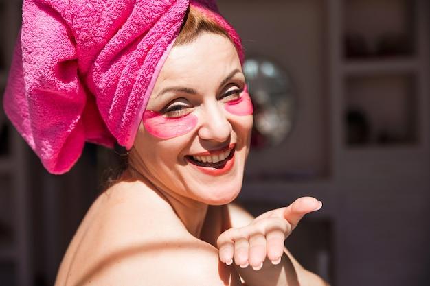 Hermosa mujer con una toalla rosa en la cabeza y con parches rosas debajo de los ojos envía un beso al aire a la cámara.