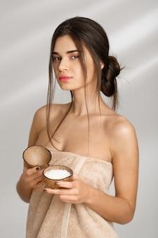 Hermosa mujer en toalla suave con exfoliante de sal antes del masaje.