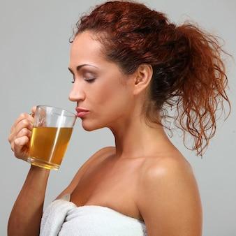 Hermosa mujer en toalla con té de hierbas
