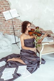 Hermosa mujer tocando el arco de violín rosa