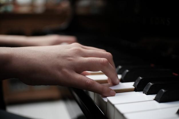 Hermosa mujer tocando el piano, aprende a tocar el piano.