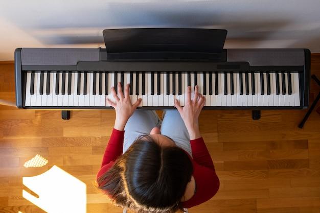 Hermosa mujer tocando el piano en casa