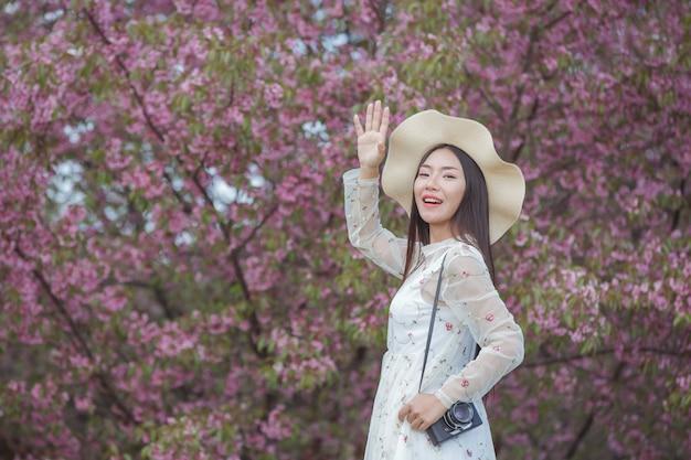 Una hermosa mujer toma una foto con una cámara de cine en el jardín de flores de sakura.