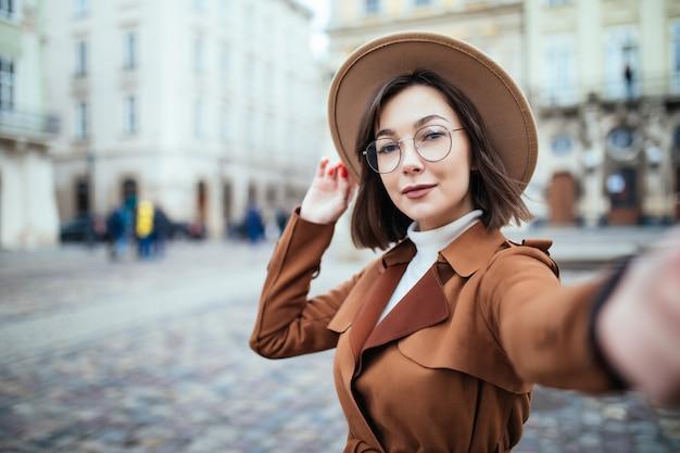 Hermosa mujer toma selfie mientras sostiene su teléfono en la ciudad
