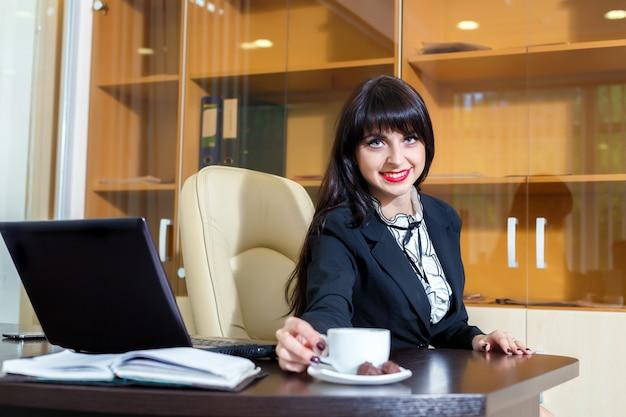 Hermosa mujer toma una taza de café en una mesa en la oficina