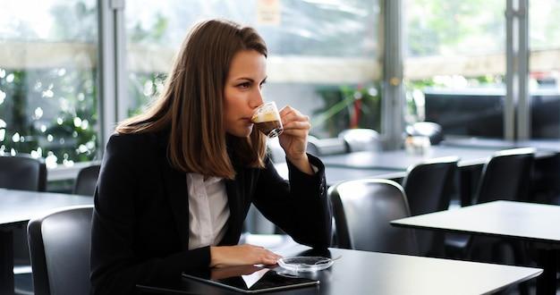 Hermosa mujer tomando un café en una cafetería