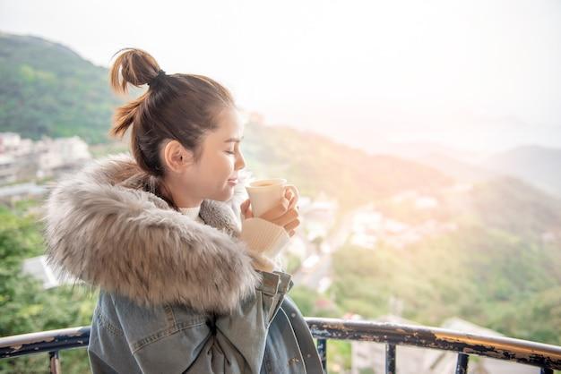 Hermosa mujer está tomando café en la mañana con fondo de naturaleza