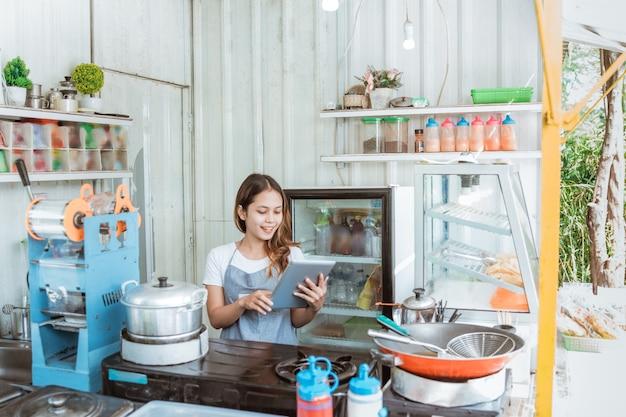 Hermosa mujer tomando pedidos en línea en su pequeña tienda. joven propietario de una pequeña empresa