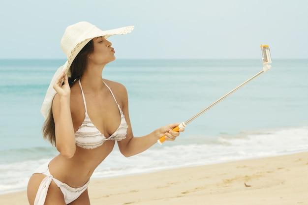 Hermosa mujer está tomando selfie en la playa