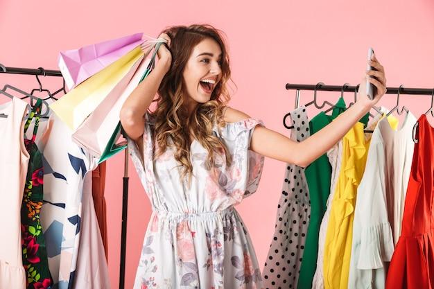Hermosa mujer tomando selfie en teléfono inteligente en la tienda cerca de perchero con coloridas bolsas de compras aisladas en rosa