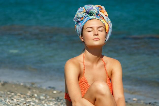 Hermosa mujer tomando el sol en la playa