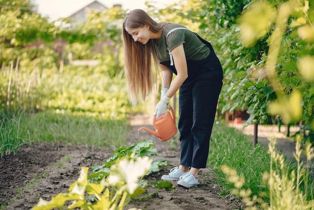 Hermosa mujer trabaja en un jardín cerca de la casa