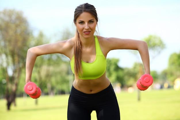 Hermosa mujer trabajando con pesas