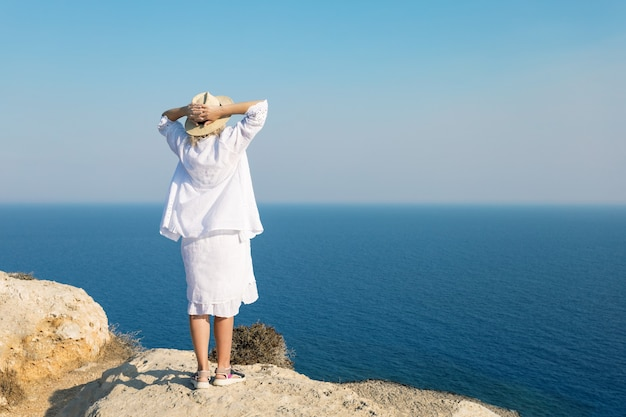 Hermosa mujer en traje de baño blanco vestido de pie en la cima del acantilado y mirando al mar, disfrutando de la libertad. viajar, vacaciones, concepto.