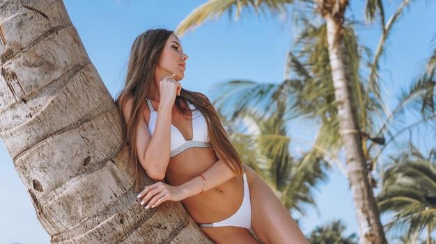 Hermosa mujer en traje de baño junto al mar junto a la palmera