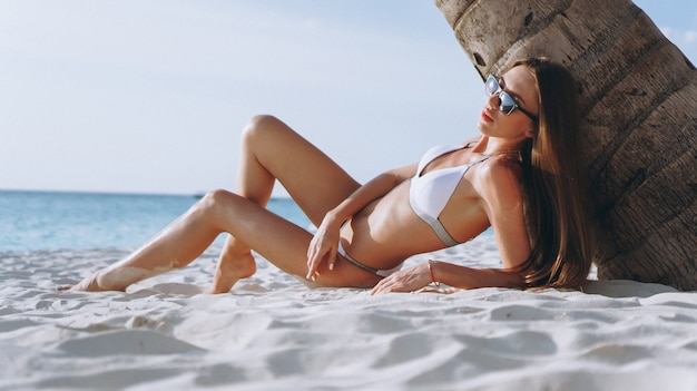 Hermosa mujer en traje de baño por el océano tumbado debajo de la palma