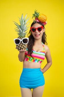Hermosa mujer en traje de baño sosteniendo una piña posa en amarillo