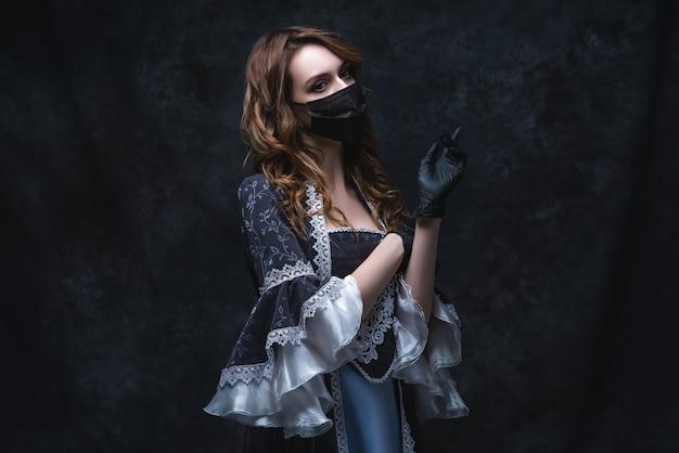 Hermosa mujer en traje renacentista, mascarilla y guantes, concepto antiguo y nuevo