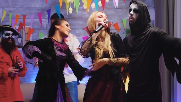 Hermosa mujer en traje de repetición cantando karaoke en la fiesta de halloween. grupo de amigos bailando y divirtiéndose en el fondo