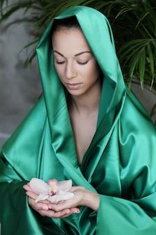 Hermosa mujer con traje tradicional indio y flores en las manos