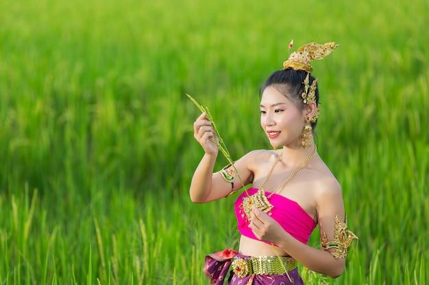 Hermosa mujer en traje tradicional tailandés sonriendo y de pie en el templo