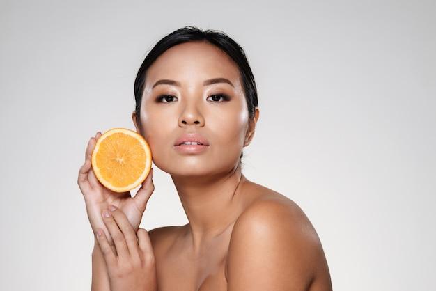Hermosa mujer tranquila mostrando rodaja de naranja y mirando a cámara