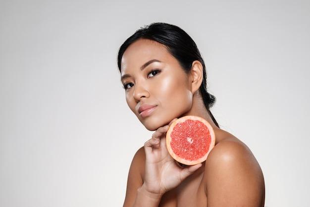 Hermosa mujer tranquila mostrando rodaja de pomelo