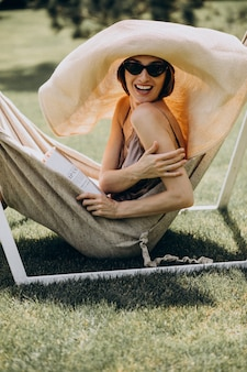 Hermosa mujer tumbada en una hamaca con sombrero grande