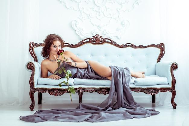 Hermosa mujer tumbada en el sofá y sosteniendo una rosa roja