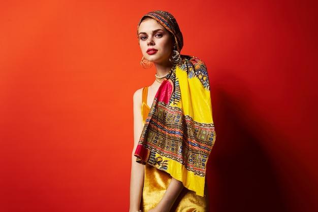 Hermosa mujer en turbante multicolor atractivo look joyería fondo rojo