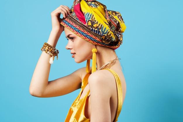 Hermosa mujer en turbante multicolor modelo de estudio de sonrisa de joyería de mirada atractiva