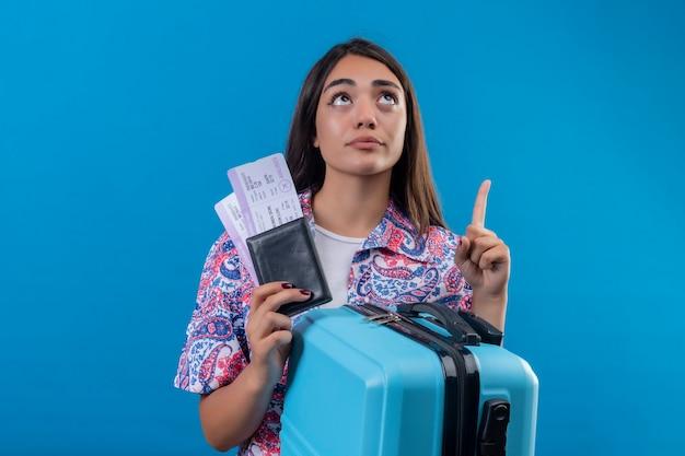 Hermosa mujer turista con maleta de viaje y pasaporte con boletos mirando hacia arriba y apuntando con el dedo índice pensando en concepto de viaje incierto de pie sobre el espacio azul