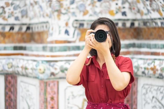Hermosa mujer turista sostiene cámara para capturar los recuerdos.