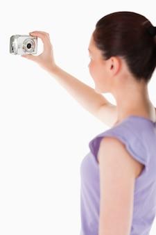 Hermosa mujer usando una cámara mientras está de pie